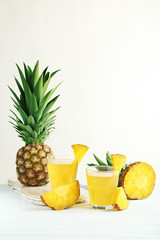 Glasses of pineapple juice on a white wooden table