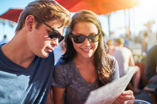 couple looking at menu seated in outdoor restaurant
