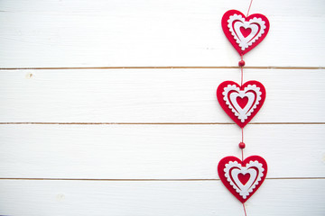 Frame of hearts hanging on white painted wooden background