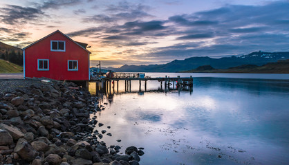 Red fisher man house seaside with private jetty with rocky dam foreground during sunrise at Eskifjorour Iceland