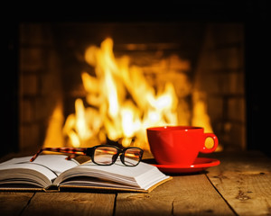 Red cup of coffee or tea, glasses and old book on wooden table n
