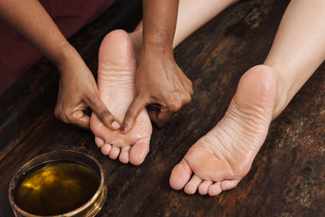 Ayurvedic foot massage with oil on the wooden table
