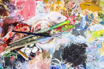 Artist palette with a Cup for mixing oil paints and brushes with