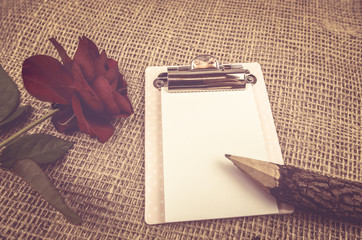 Wooden pencil on a notebook in romantic decor - Idyllic image with a wooden pencil on a notebook, accompanied by a red rose and a hemp fabric as decor.