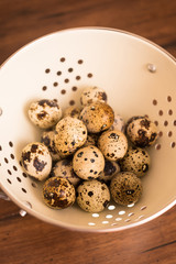 Quail eggs in a colander on a wooden rustic table, selective focus