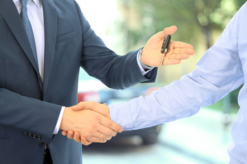 Car salesman handing over the keys for a new car to a young busi