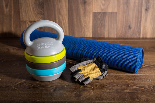 Adjustable kettlebell, cycle gloves dumbbells and yoga mat on wooden background. Weights for a fitness training.