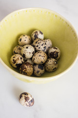 Quail eggs in a bowl on a table, selective focus
