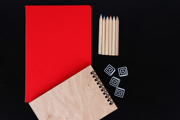 Notebooks with coloured pencils and clips on black table