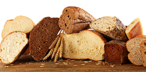 Cut fresh baked bread and wheat ears, isolated on white