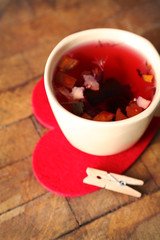Cup of fruit tea on red heart with clothespin on wooden background closeup