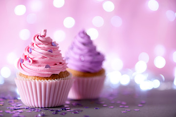 Two cupcakes on a glitter background, close up