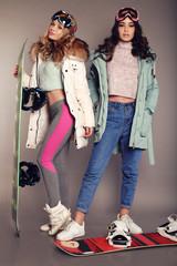 two beautiful skier girls wear ski equipment