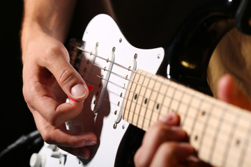 Male hands playing electric guitar with plectrum closeup