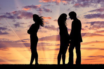 Silhouette of a lonely woman near loving couple