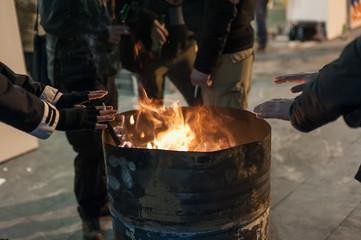 Homeless man warming his hands by a fire / Poor men warm outdoors near smoking barrel