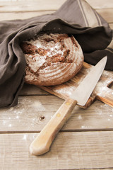 Fresh bread and salt on a wooden background
