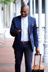 African business man traveling with bag and cell phone.