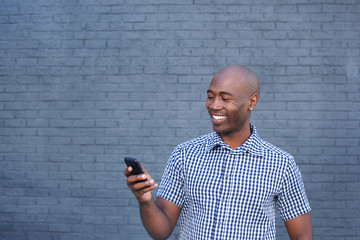 Smiling african man looking at mobile phone