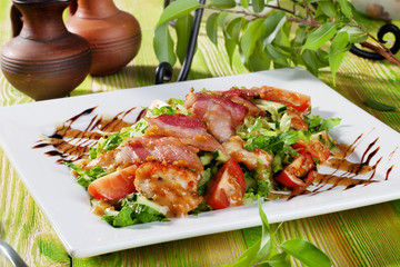 Still salad with chicken nuggets, arugula, bacon, tomatoes, balsamic sauce on a wooden table