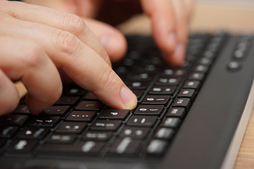 Closeup of fingers typing on computer keyboard