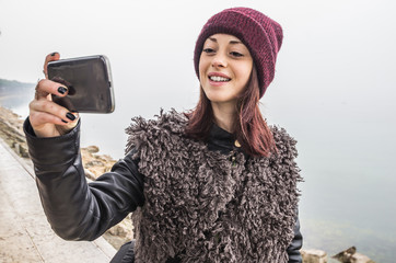 Attractive caucasian girl is taking a selfie outdoor during the winter season - people, lifestyle and technology concept