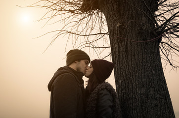 Couple of lovers is kissing under a tree during the autumn season - people, love and nature concept