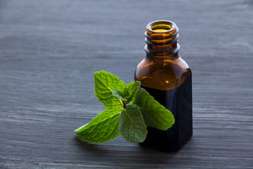 Essential aroma oil with peppermint  on wood