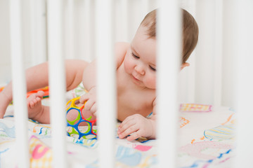 baby playing in a crib
