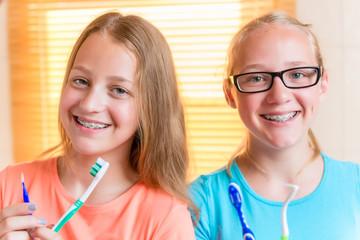Schwestern im Bad mit Zahnspange putzen Zähne