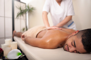 Masseur doing back massage on man body in the spa salon