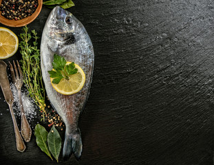 Fresh sea fish placed on dark stone background
