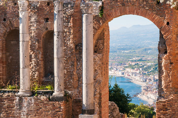 View of some columns and one arch in the scene of the greek theater in Taormina and a perspective of Giardini Naxos in the background Wall mural