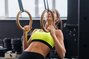 Athlete fit woman exercising in gym pulling up on gymnastic rings.