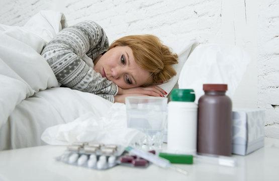sick woman feeling bad ill lying on bed suffering headache winter cold and flu virus having medicines