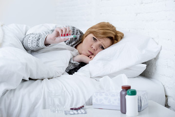 sick woman in bed checking temperature with thermometer feeling feverish having cold winter flu virus