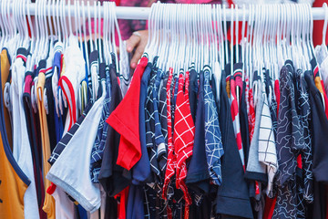 Choice of fashion clothes of different colors on hangers
