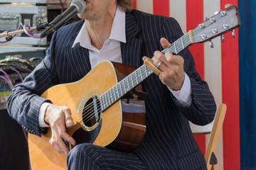 Wooden guitar in musician hands