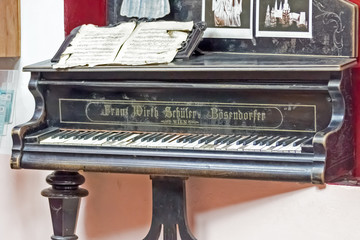 Old piano with one leg on the cover and notes