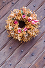 Decorative wreath with small roses on a wooden surface