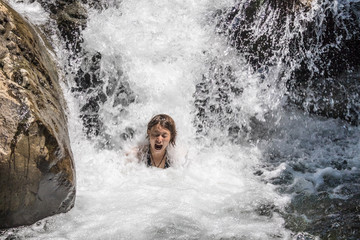 Young girl swimming in the water at the waterfall