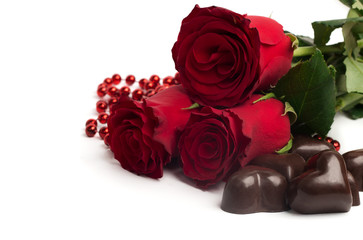 Red roses and candies in a shape of a heart isolated