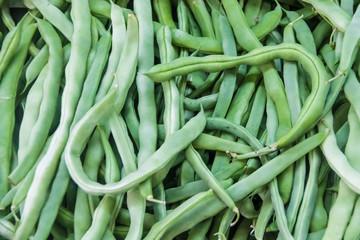 Pile of fresh green bean legumes at farmers market stall.