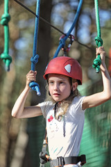 pensive girl in a helmet took up the challenge and goes on an adventure ropes course