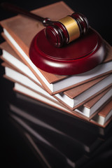 judge's gavel and law books on a black table