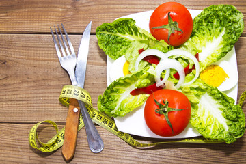 table salad with cutlery on wooden background