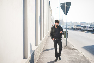 Young handsome caucasian bearded man walking in the city holding