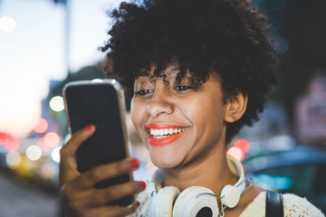 Portrait of young handsome afro woman holding a smartphone, look