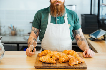 Bearded man in apron standing and holding tongs for croissants