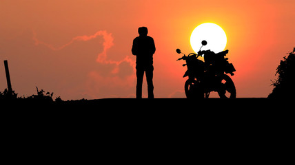 A man and motorcycle over sunset.